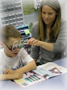 woman helping child with vision therapy
